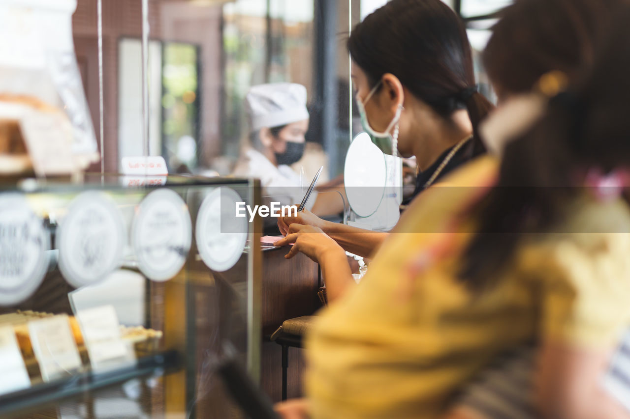Woman customer in protective mask signing on receipt at counter in cafe