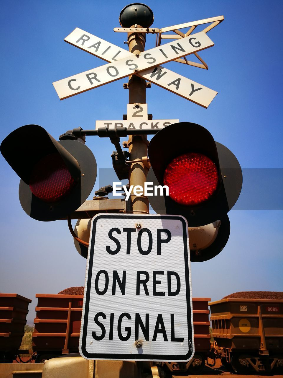 guidance, communication, road sign, crossing sign, railroad crossing, western script, text, low angle view, railway signal, direction, day, clear sky, warning sign, transportation, blue, red light, safety, outdoors, no people, rail transportation, stoplight, sky, one way, illuminated, close-up