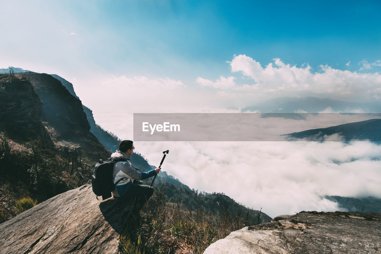 Man sitting on cliff against cloudy sky