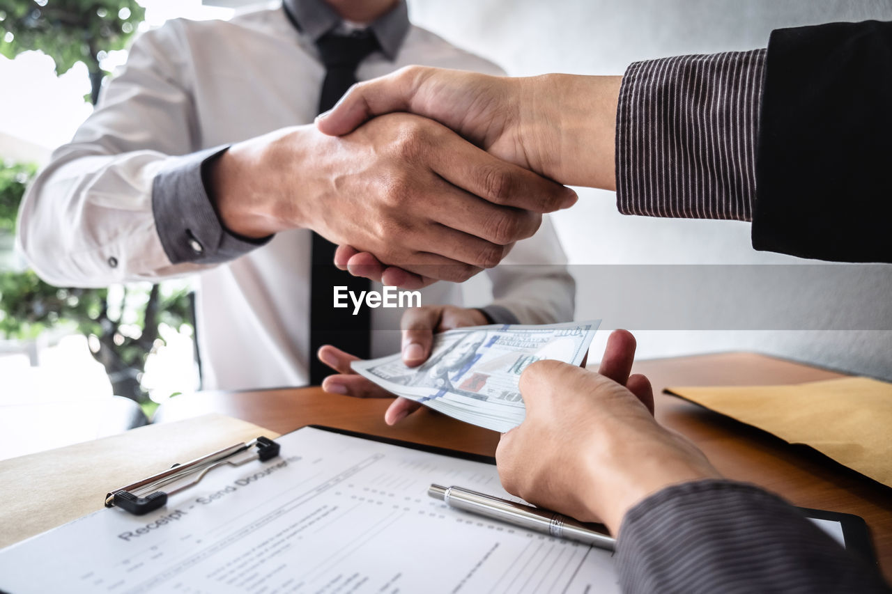 human hand, men, hand, business, occupation, two people, adult, males, businessman, human body part, business person, table, people, real people, holding, indoors, midsection, well-dressed, professional occupation, formalwear