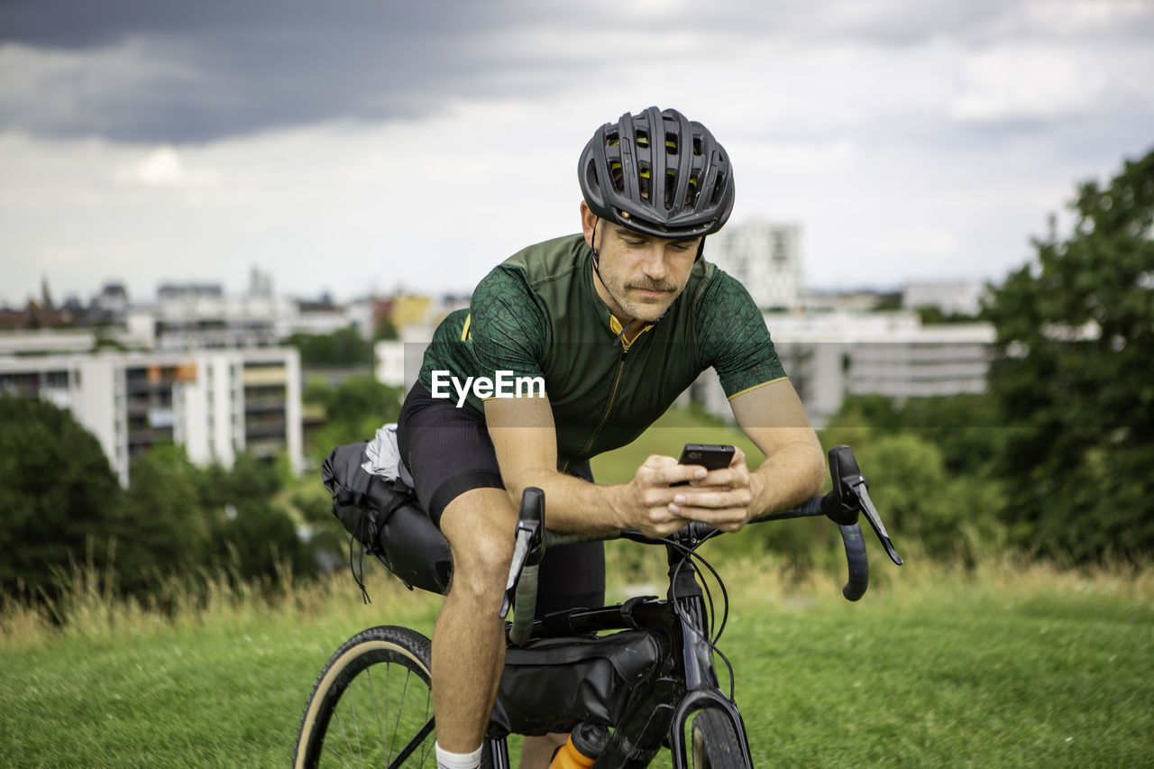 Man using mobile phone while sitting on bicycle on grassy land