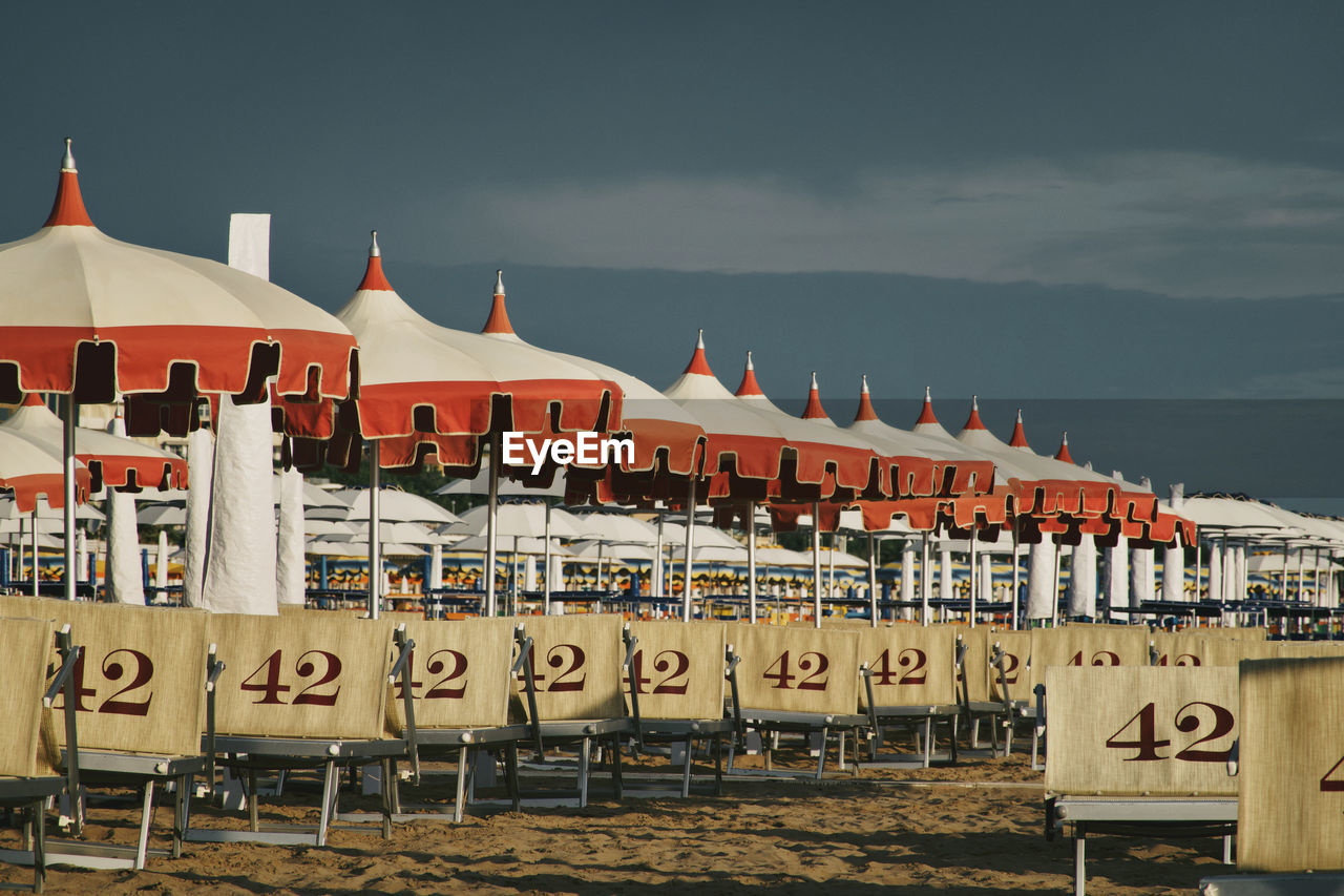 Row of beach umbrellas and numbered long chairs against sky