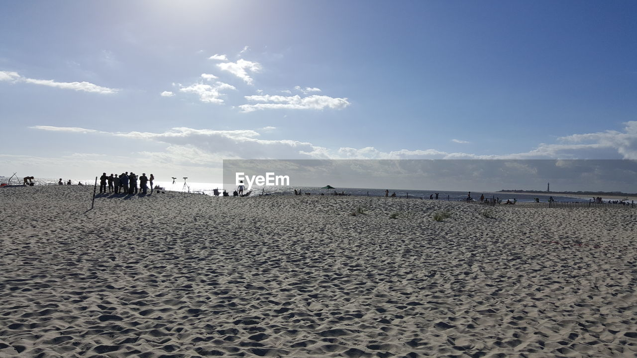 sand, beach, land, sky, scenics - nature, sea, water, cloud - sky, beauty in nature, tranquility, nature, tranquil scene, horizon, day, incidental people, horizon over water, non-urban scene, outdoors, sunlight