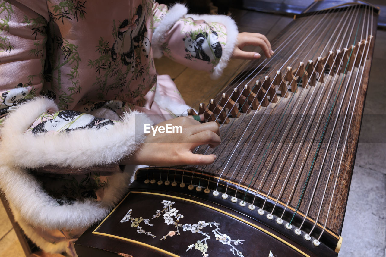 one person, arts culture and entertainment, playing, music, real people, adult, lifestyles, musical instrument, midsection, women, skill, indoors, musical equipment, high angle view, leisure activity, hand, artist, human hand, string instrument, floral pattern