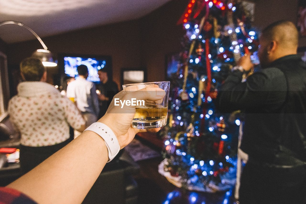 real people, celebration, human hand, indoors, alcohol, drink, illuminated, food and drink, focus on foreground, holding, christmas, lifestyles, drinking glass, leisure activity, men, human body part, night, women, close-up, one person, freshness, people
