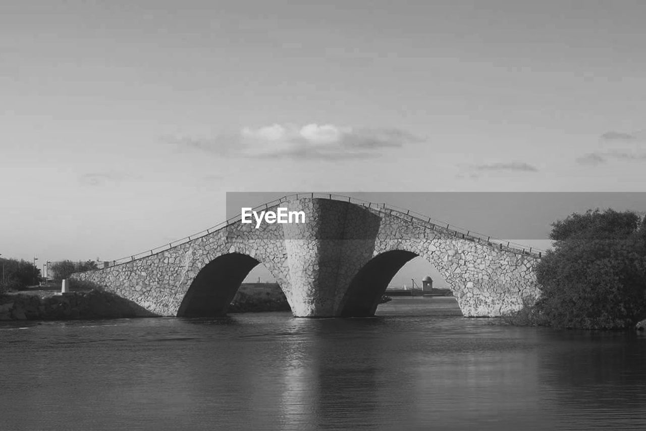 bridge - man made structure, connection, architecture, built structure, arch bridge, arch, river, cloud - sky, sky, outdoors, water, waterfront, day, no people, nature, building exterior, tree, city