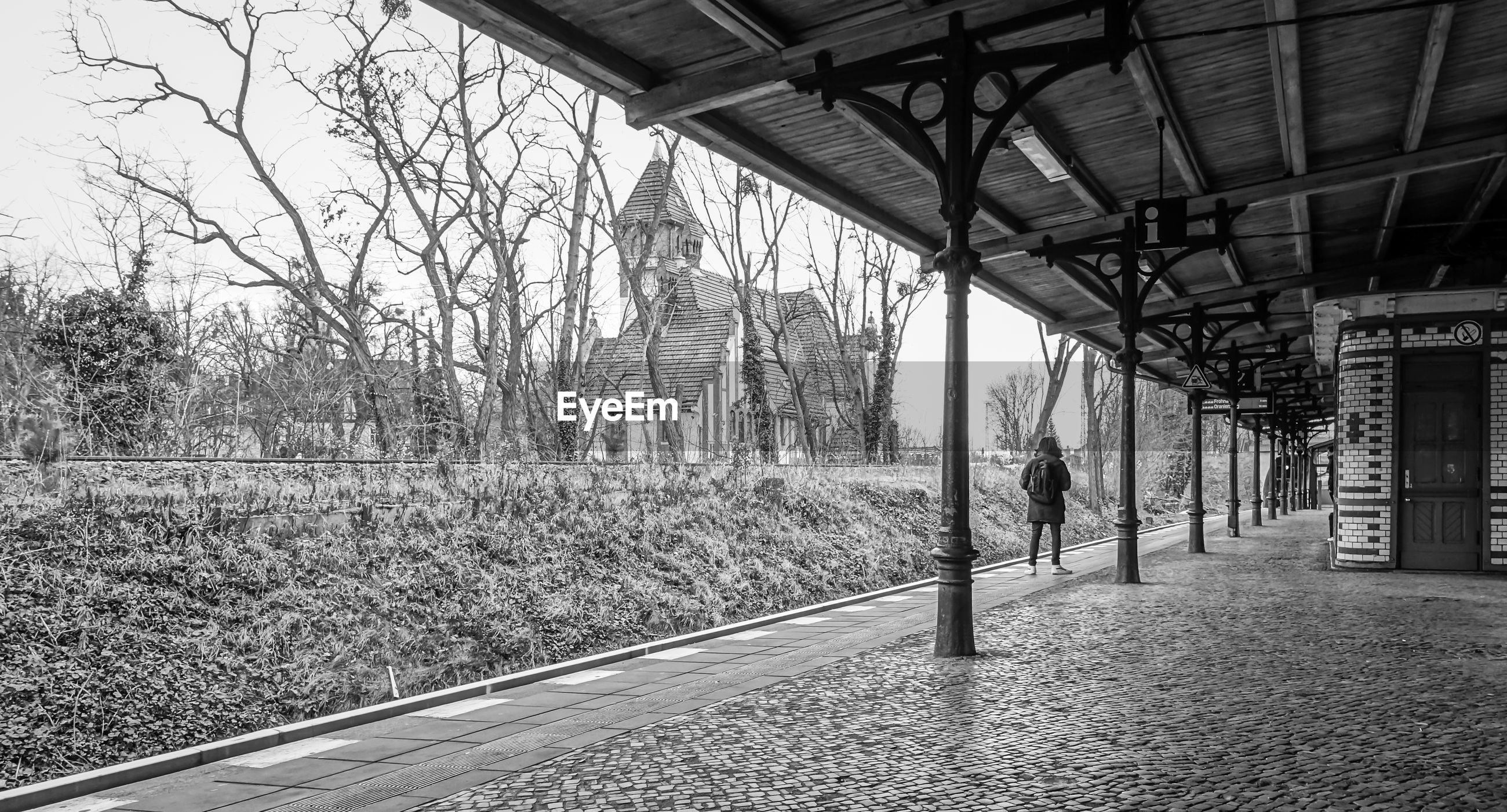 Woman standing at railroad station platform