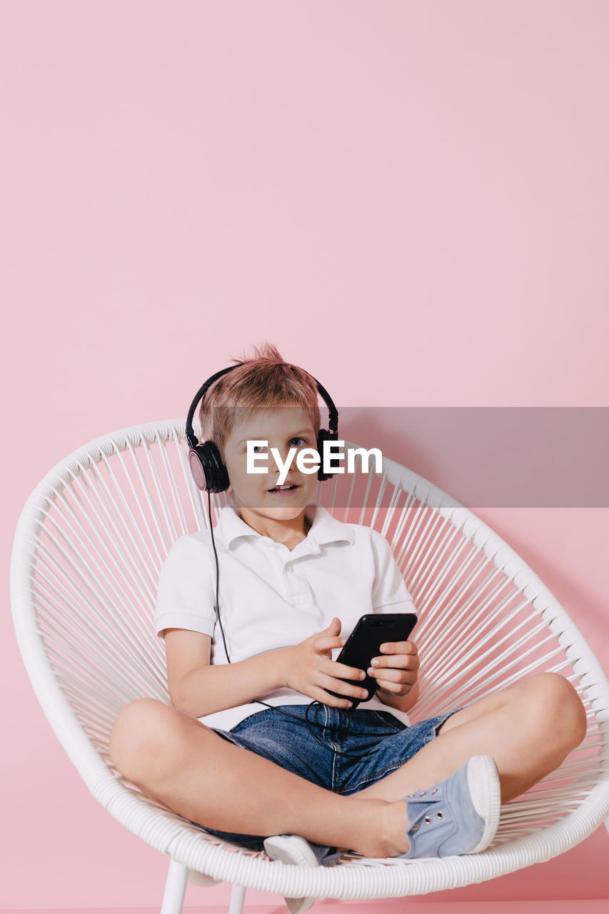 Portrait Of Boy Listening Music While Using Phone On Chair Against Colored Background