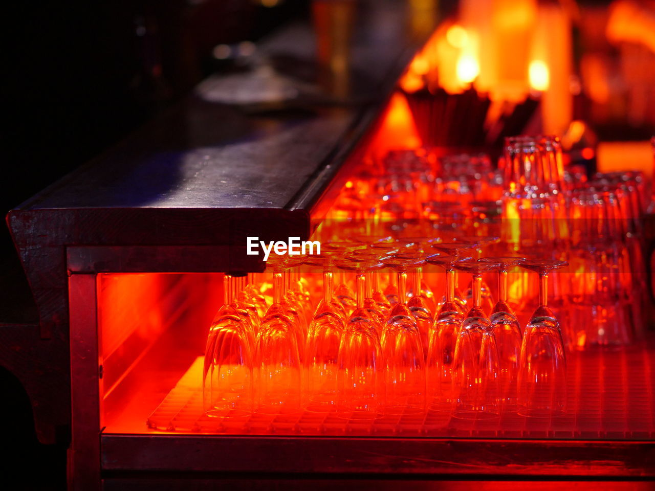 Glasses Arranged On Illuminated Table In Bar
