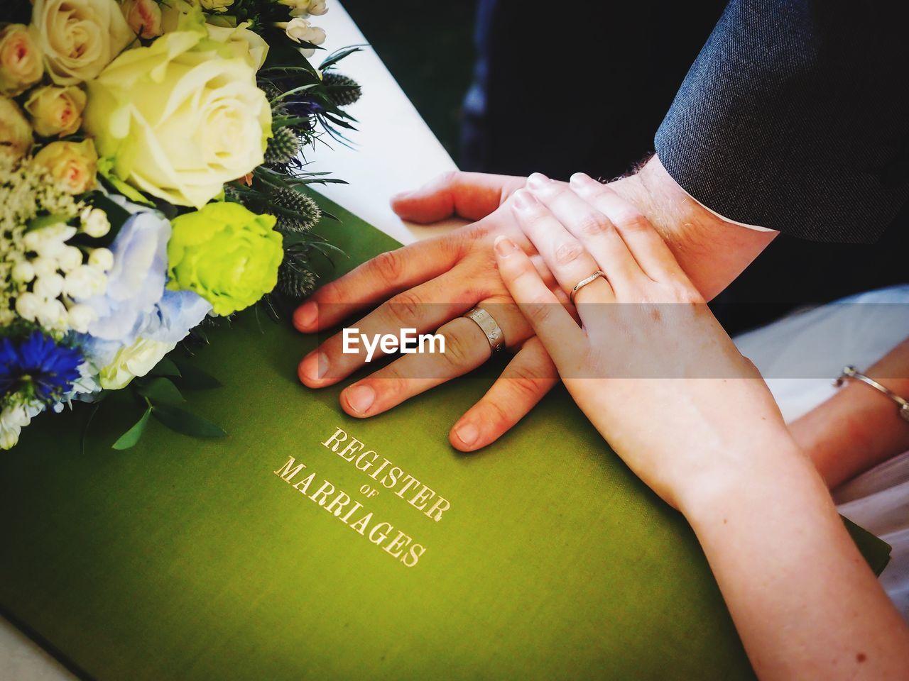 Cropped hands of bride and bridegroom on wedding register