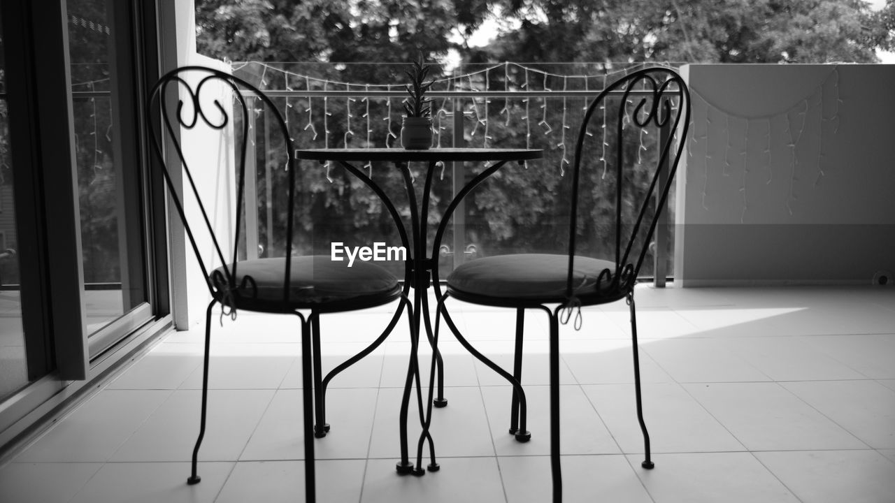 seat, chair, no people, absence, table, empty, day, flooring, indoors, tile, tiled floor, focus on foreground, architecture, metal, communication, text, still life, nature, transparent