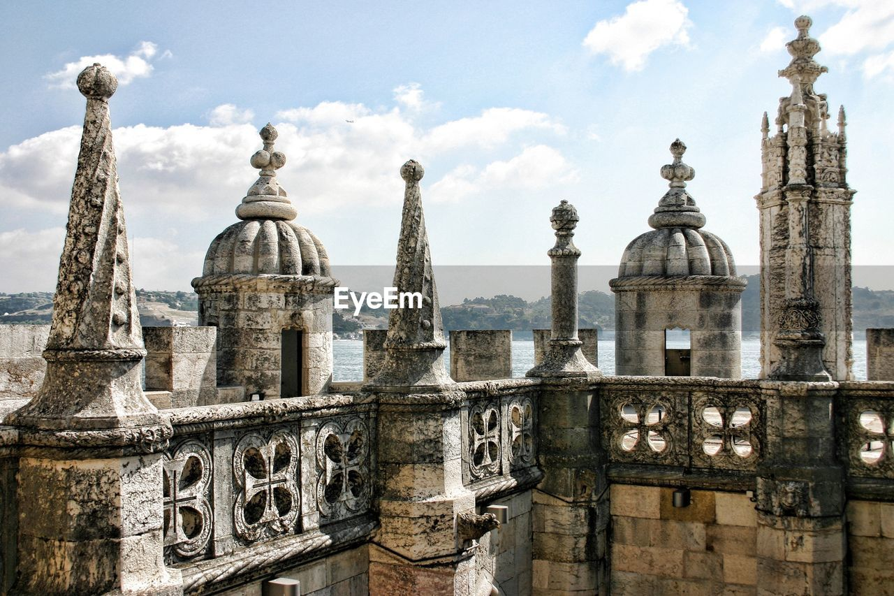 High section of torre de belem against cloudy sky
