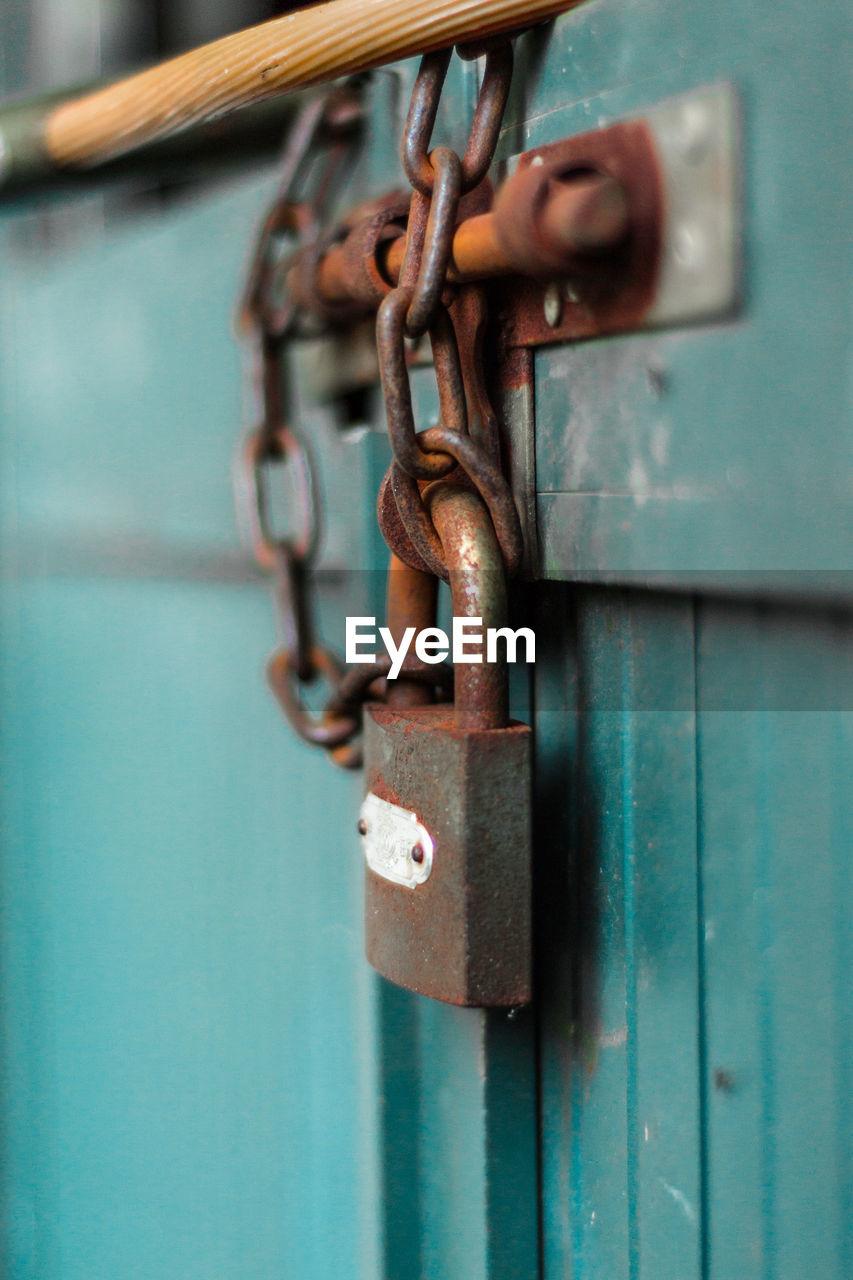 Close-Up Of Rusty Padlock Hanging On Closed Door