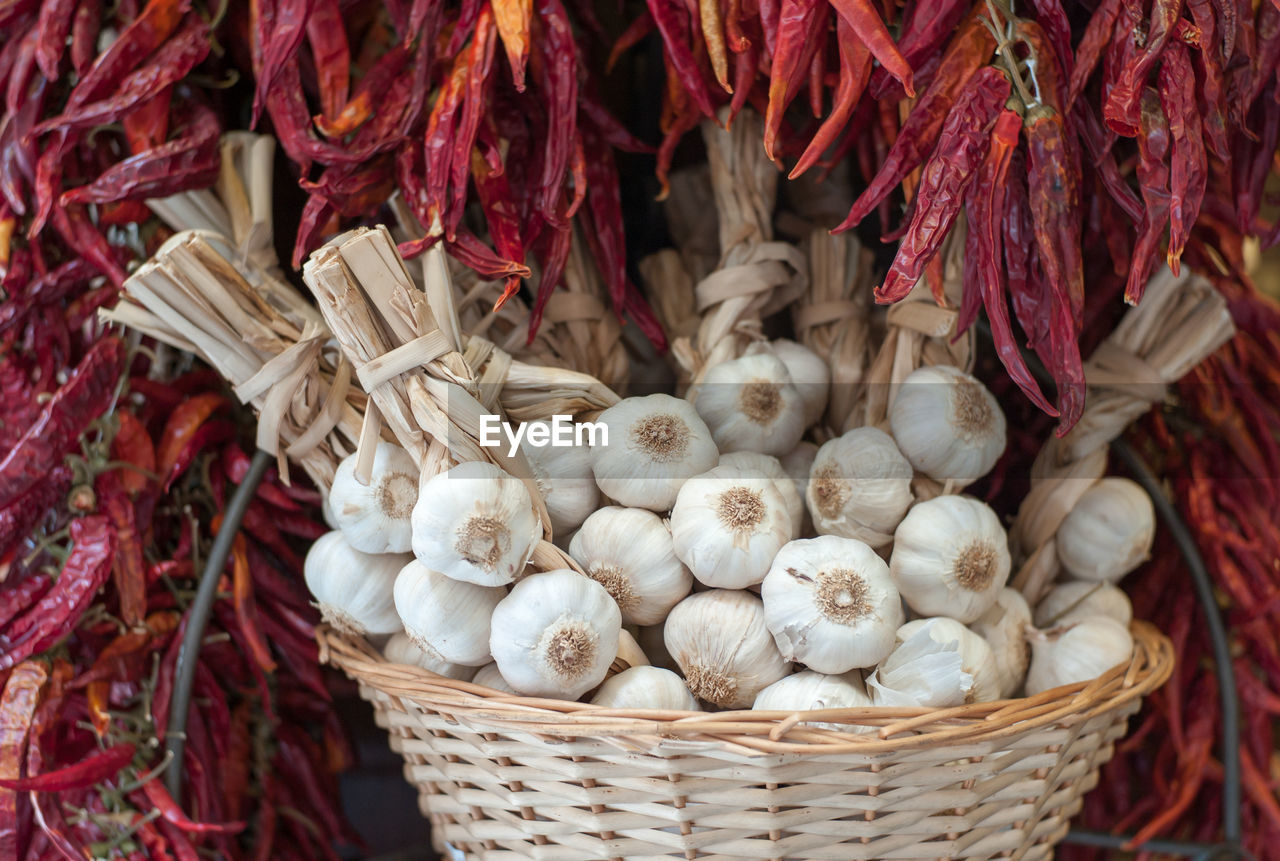 Close-up of garlic cloves in wicker basket amidst dried red chili peppers at market stall