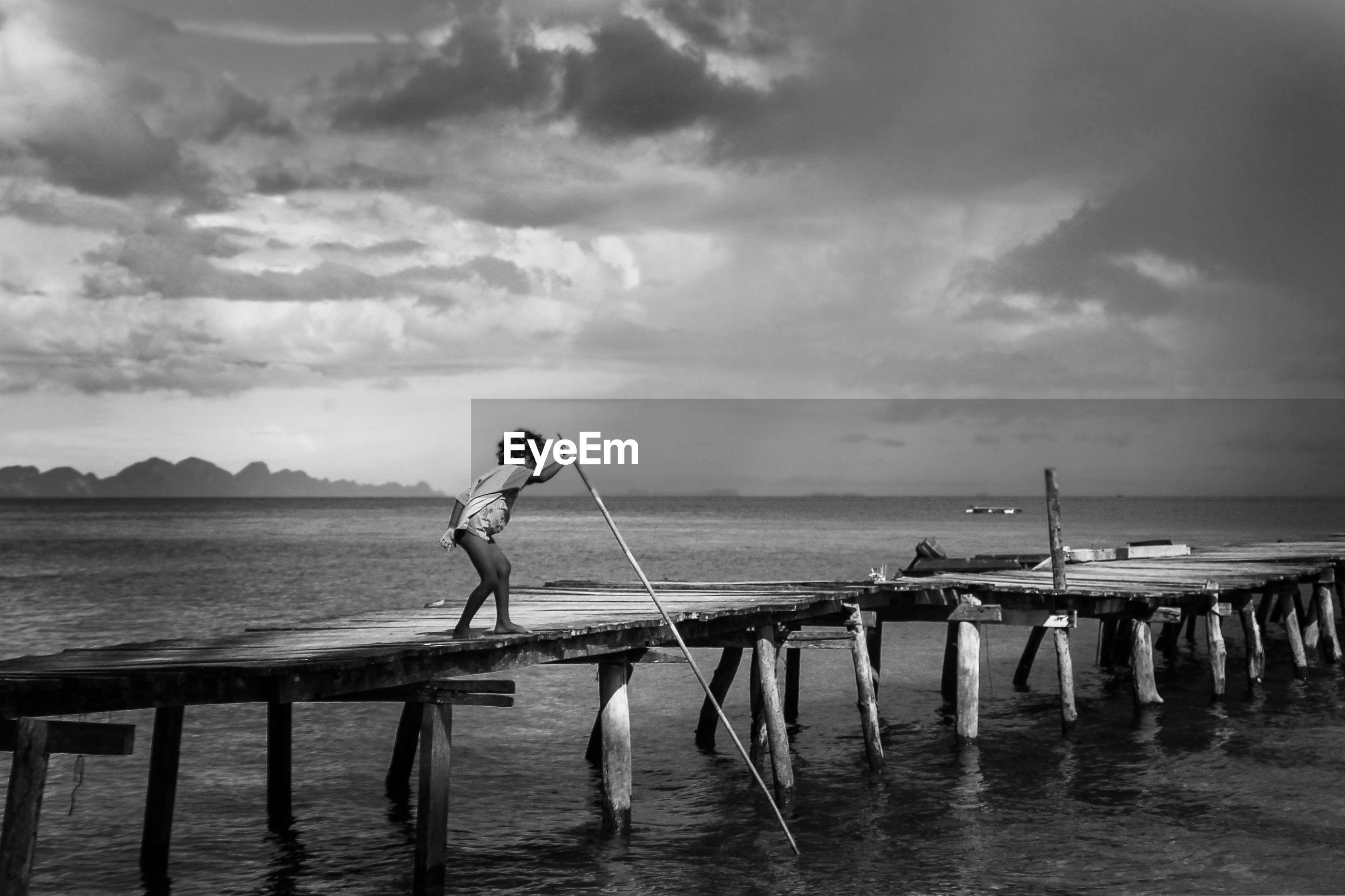 FULL LENGTH OF MAN STANDING ON PIER OVER SEA