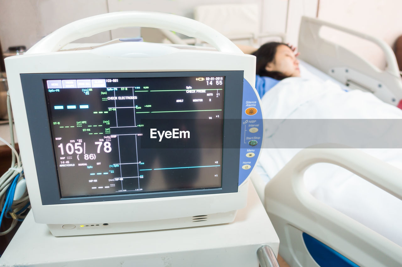 Close-Up Of Monitoring Equipment With Patient Resting On Bed In Background