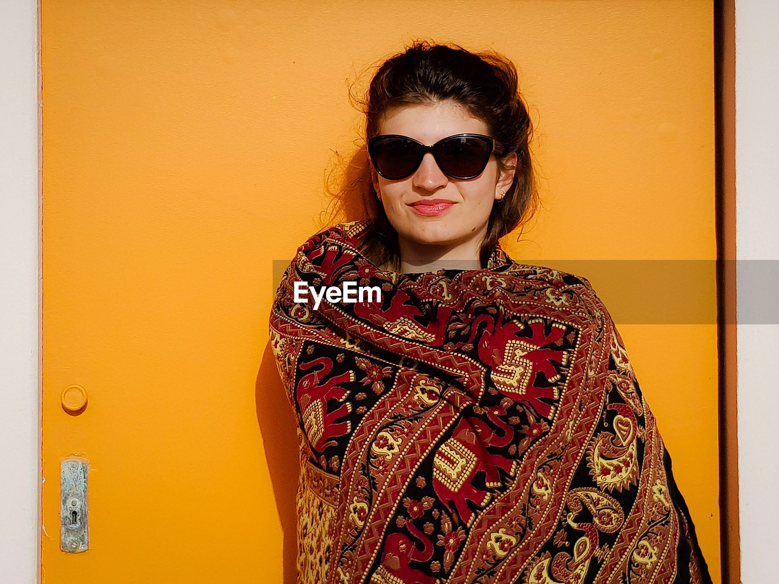 Portrait of woman in sunglasses and scarf standing against door