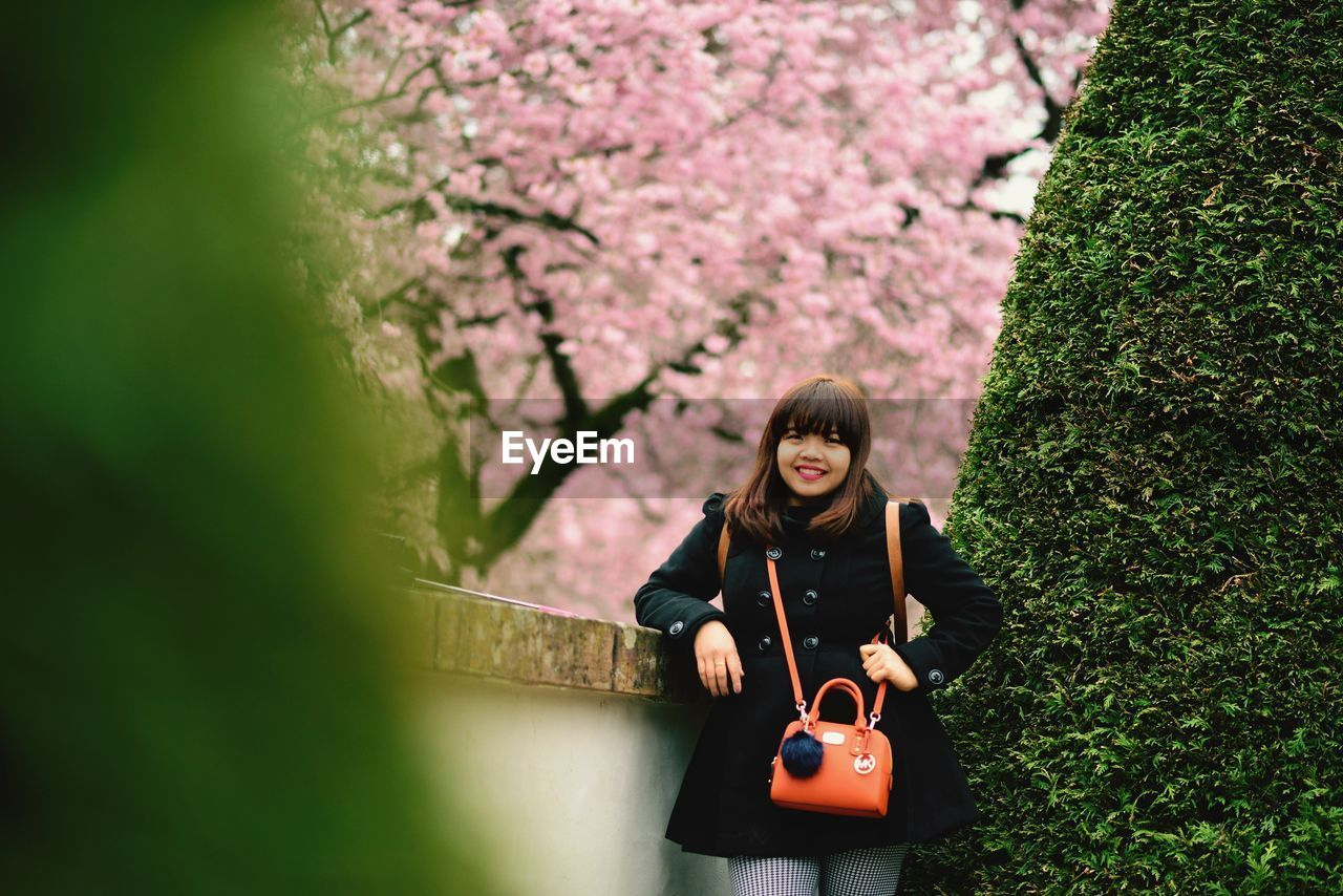 plant, front view, real people, one person, tree, leisure activity, young women, young adult, lifestyles, casual clothing, portrait, nature, growth, day, outdoors, women, flowering plant, green color, flower, hairstyle, springtime, beautiful woman, cherry blossom