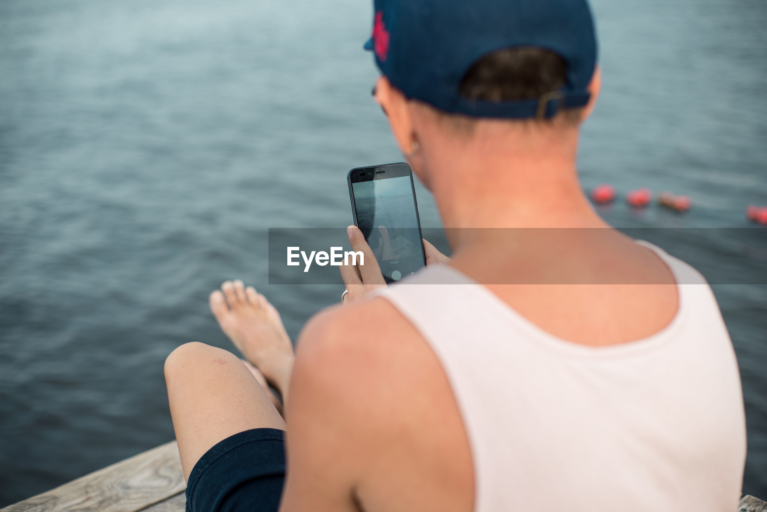 Rear view of man using mobile phone by sea