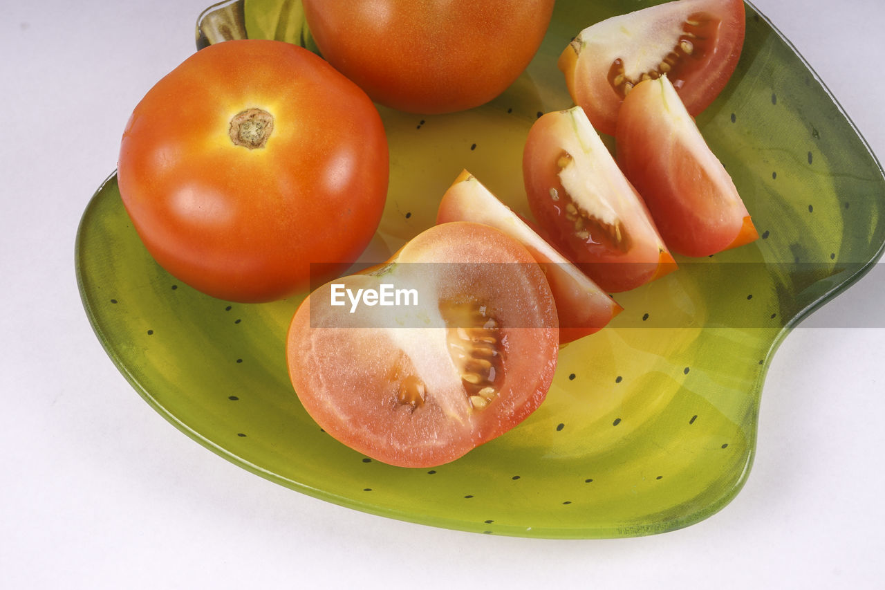 fruit, healthy eating, food and drink, food, freshness, wellbeing, still life, indoors, no people, tomato, slice, close-up, table, vegetable, red, high angle view, white background, green color, group of objects, cross section, ripe