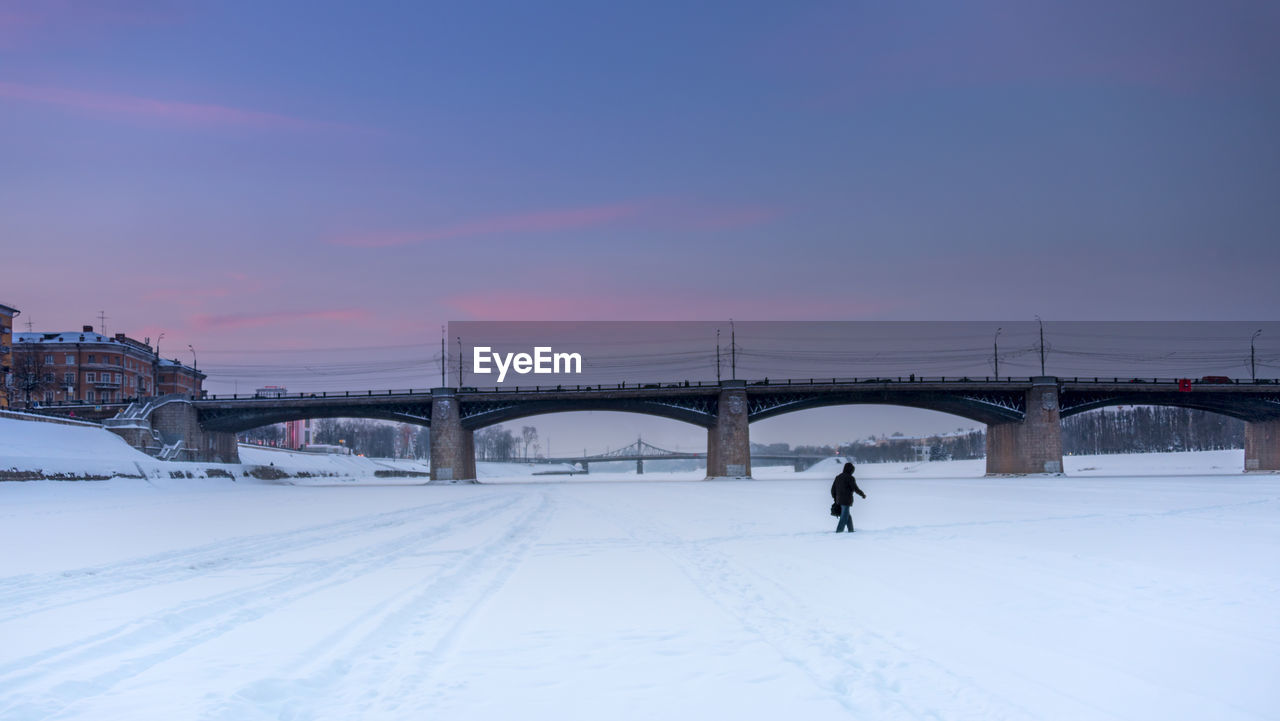 built structure, architecture, connection, sky, bridge, bridge - man made structure, transportation, cold temperature, winter, snow, nature, building exterior, city, sunset, real people, one person, engineering, travel, travel destinations, outdoors, warm clothing