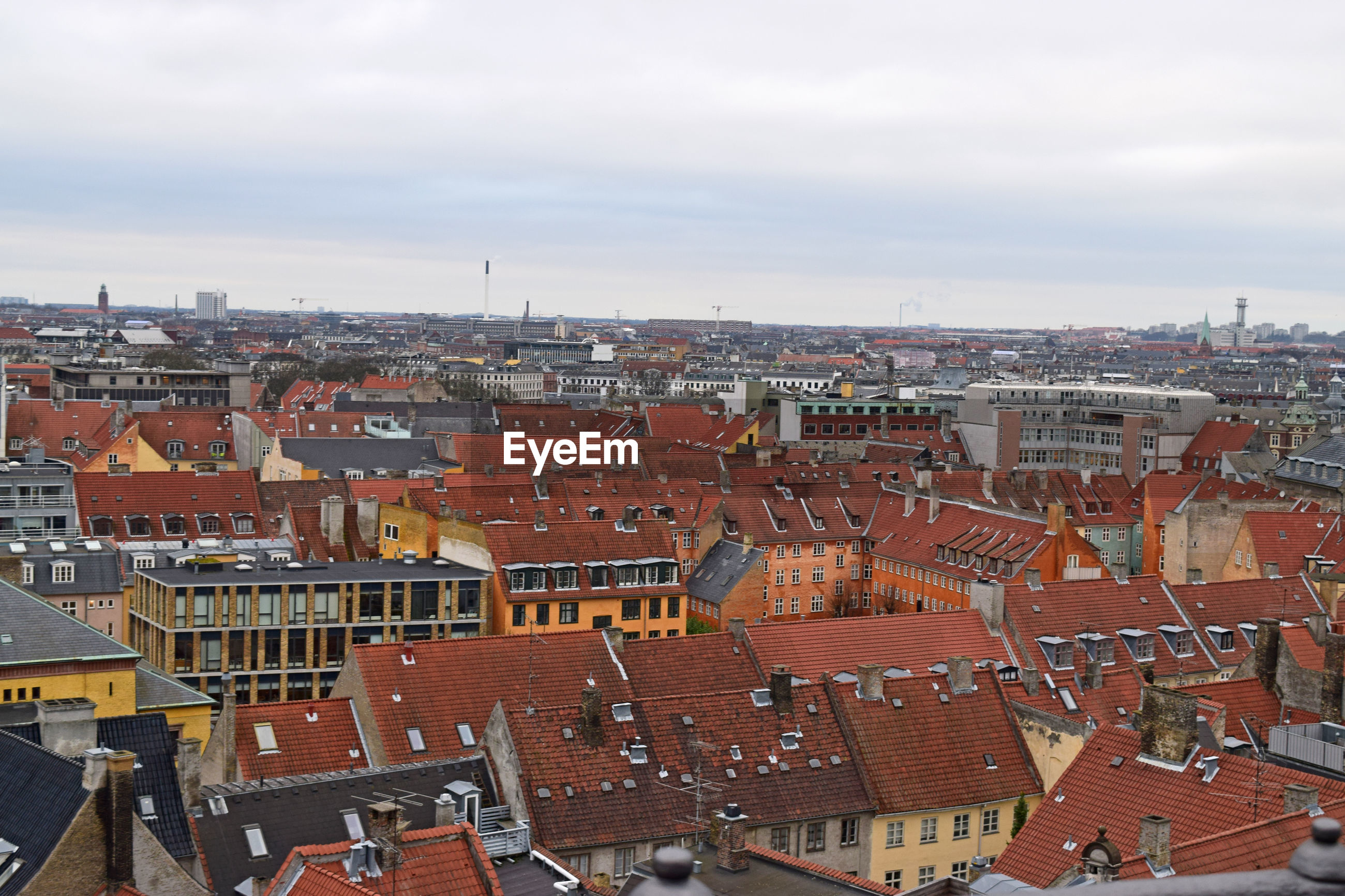 HIGH ANGLE VIEW OF HOUSES AGAINST SKY IN CITY