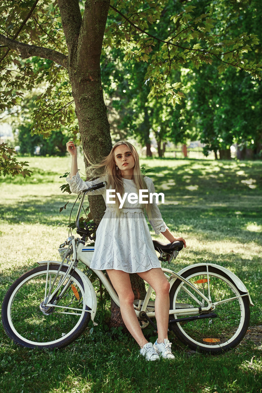 Pretty blond girl in white dress with bike near trees resting
