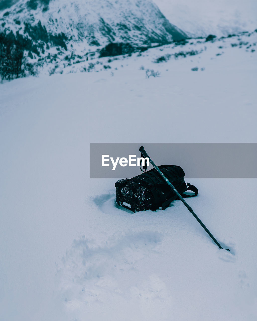 High angle view of backpack and hiking pole on snowy land