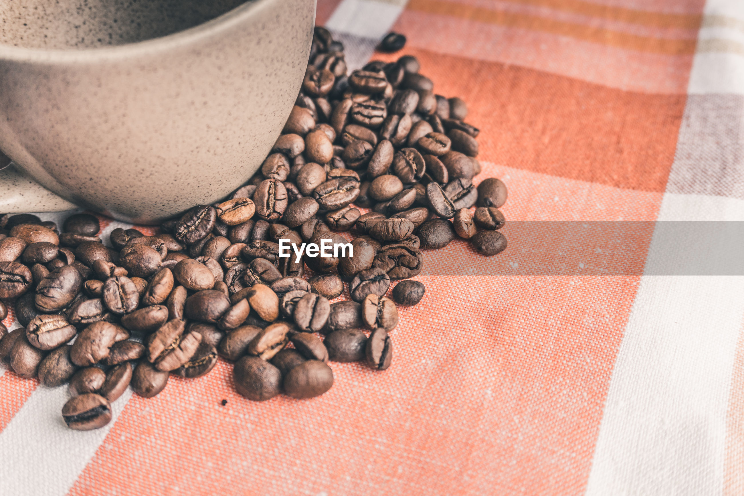 Directly above shot of coffee beans with cup on table