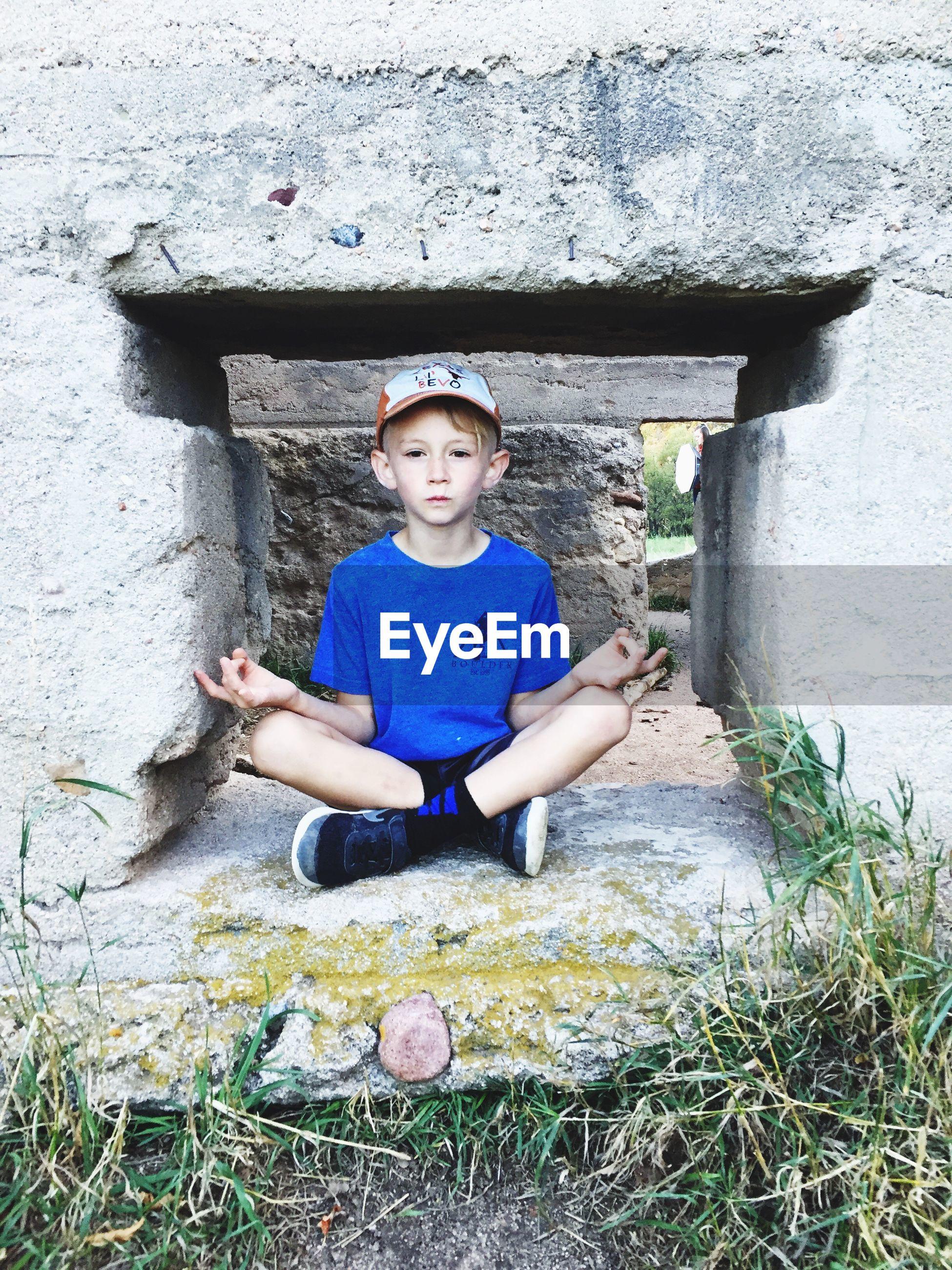 FULL LENGTH PORTRAIT OF BOY SITTING ON STONE WALL