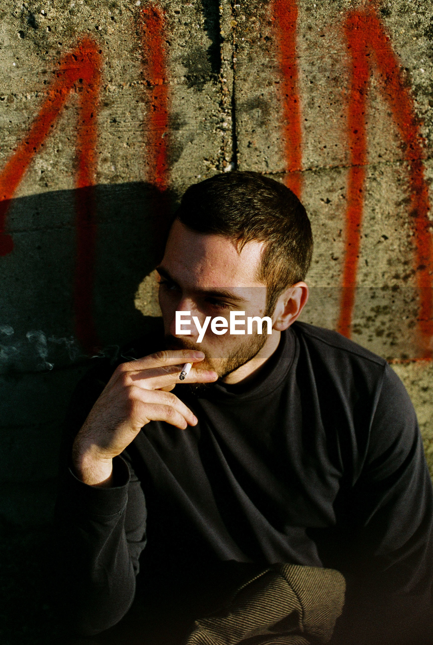 Young man smoking cigarette against wall