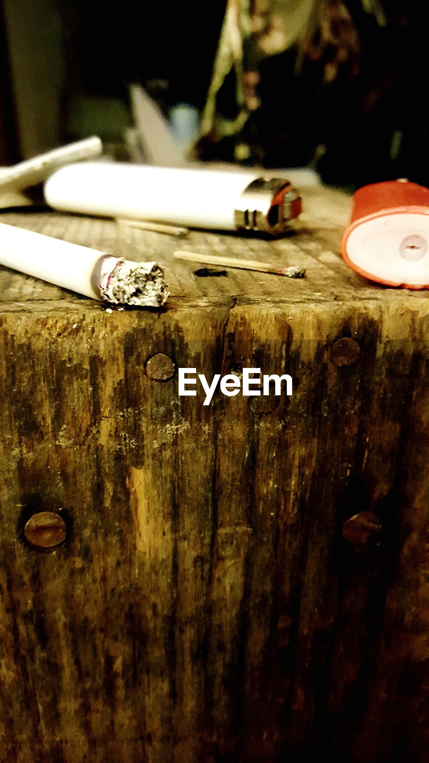 Cigarette with lighter on wooden structure