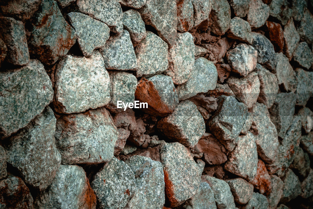 full frame, backgrounds, solid, textured, no people, pattern, close-up, large group of objects, rough, stone - object, abundance, stone material, stone wall, outdoors, day, repetition, rock, nature, wall, rock - object