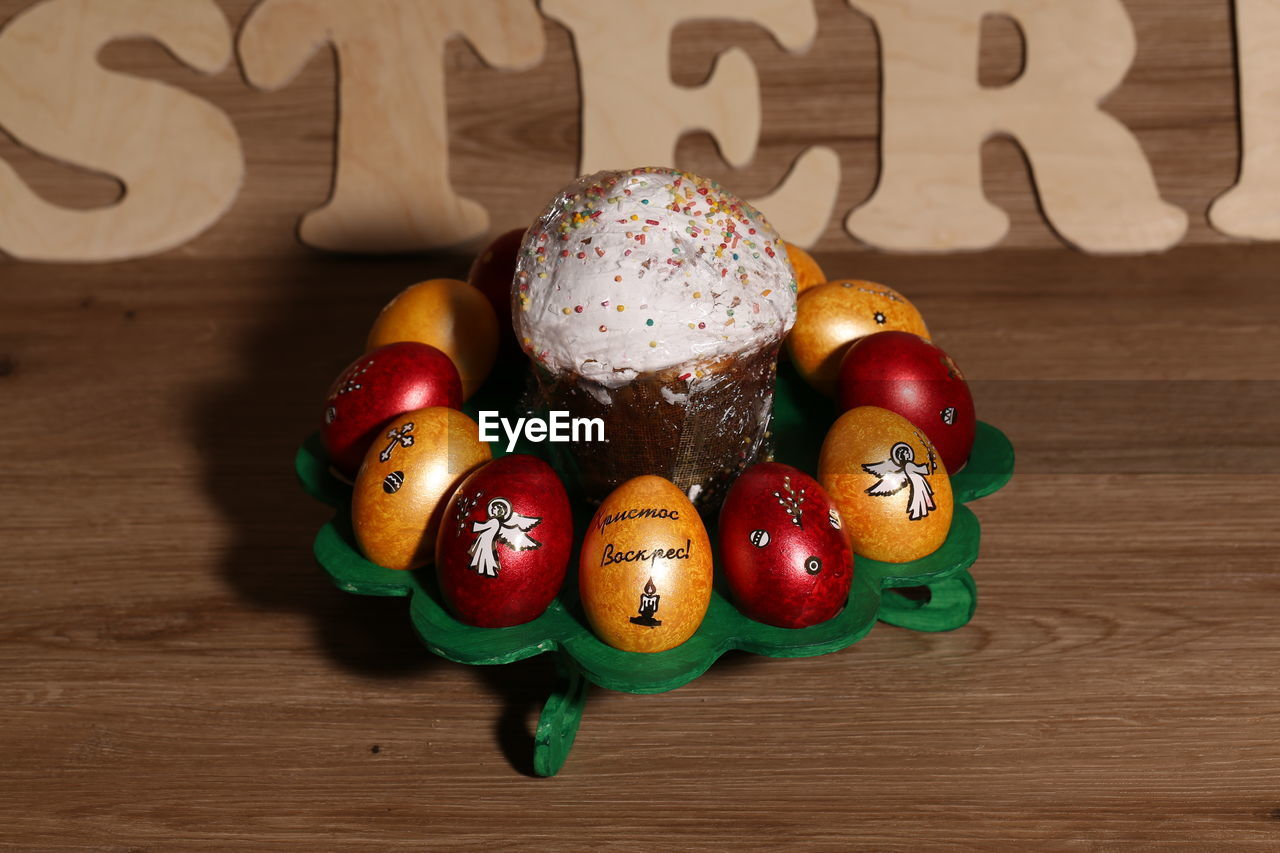 table, food, still life, indoors, food and drink, wood - material, no people, close-up, freshness, multi colored, celebration, sweet food, focus on foreground, creativity, text, easter, egg, holiday, representation