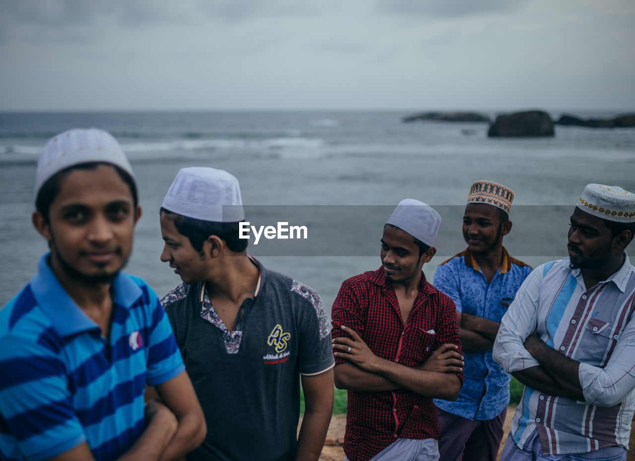 sea, real people, standing, water, outdoors, day, men, nature, horizon over water, togetherness, sky, young adult, people
