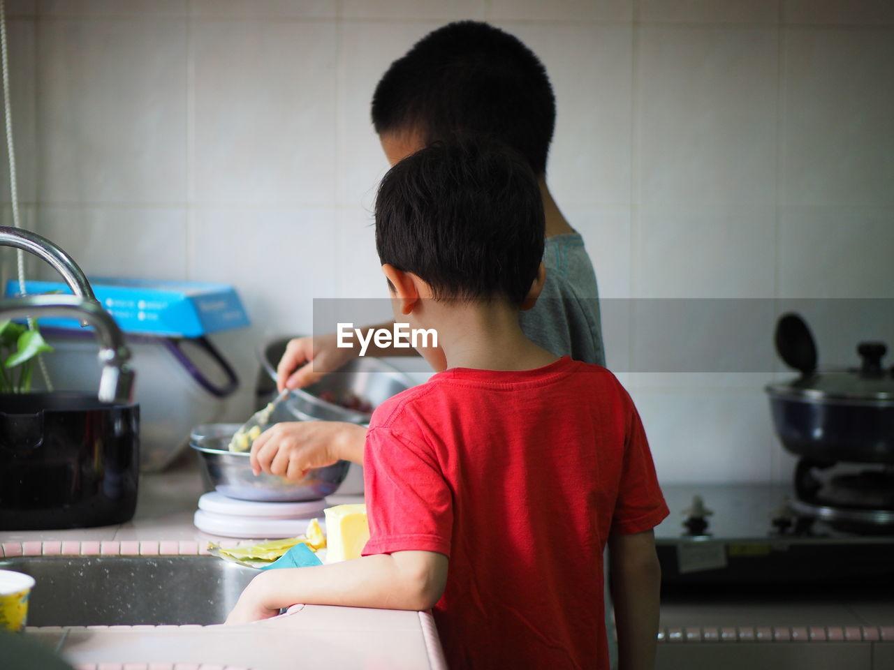 Siblings preparing food in kitchen