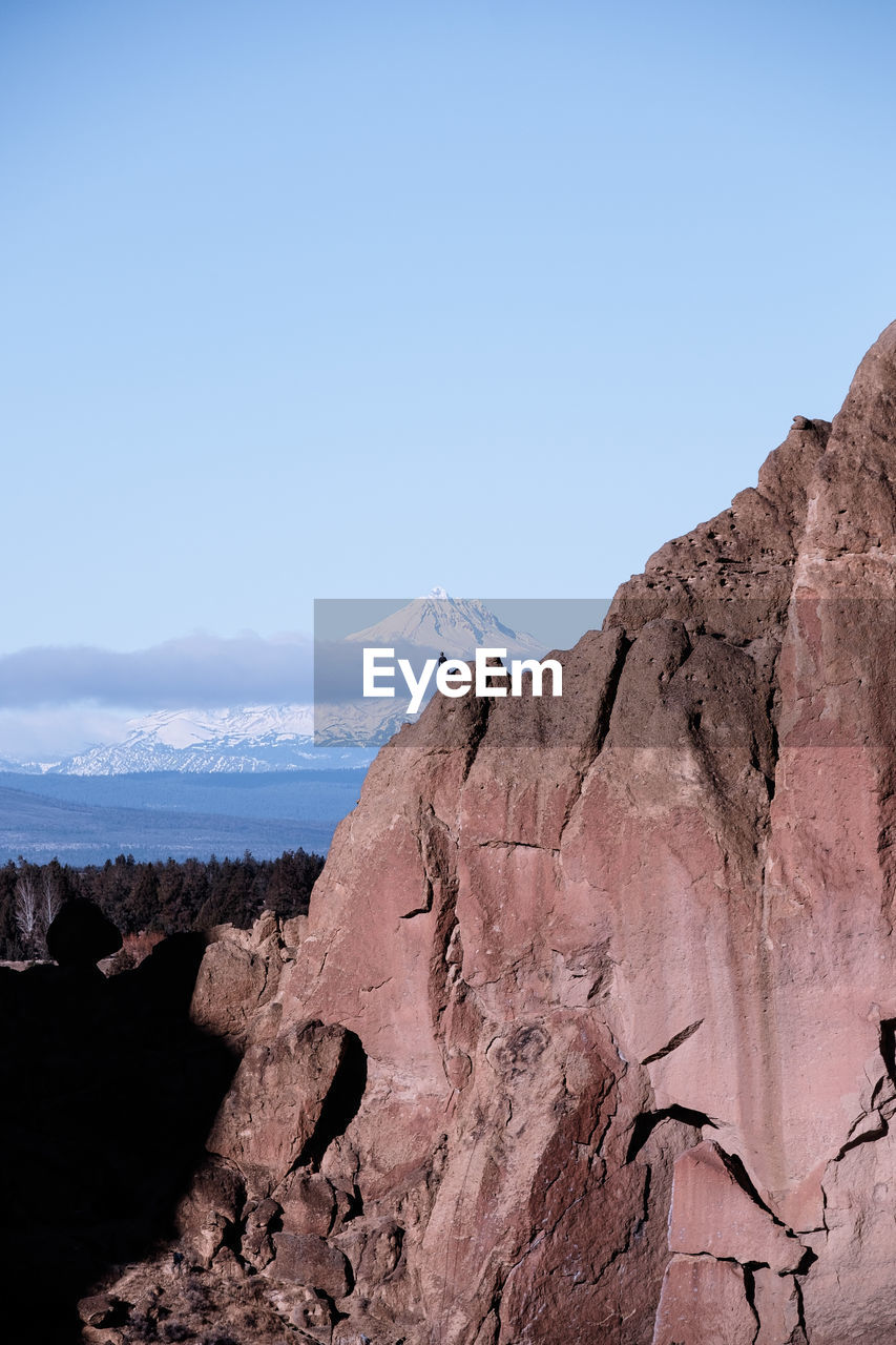 Scenic view of mountain against blue sky and rock climber