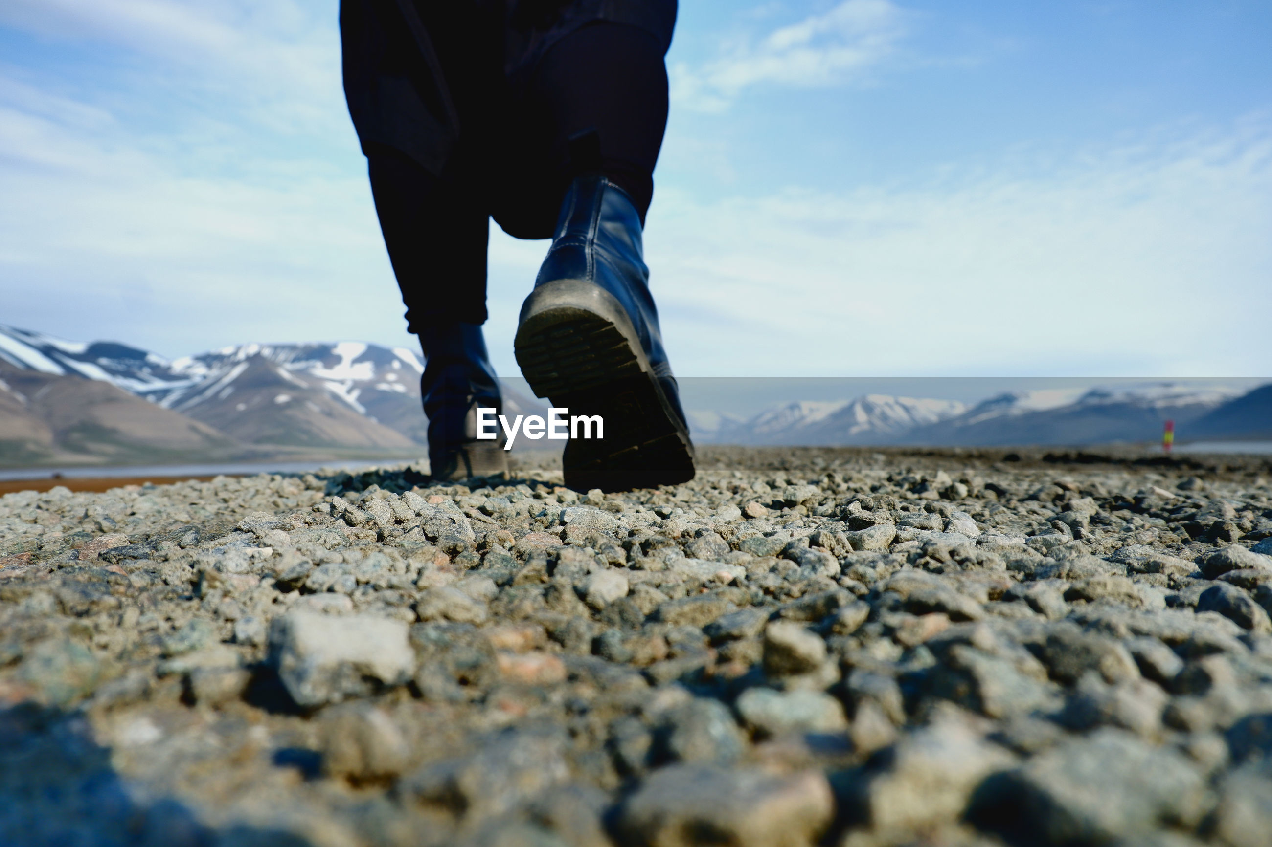 Low section of man walking on rocks against sky