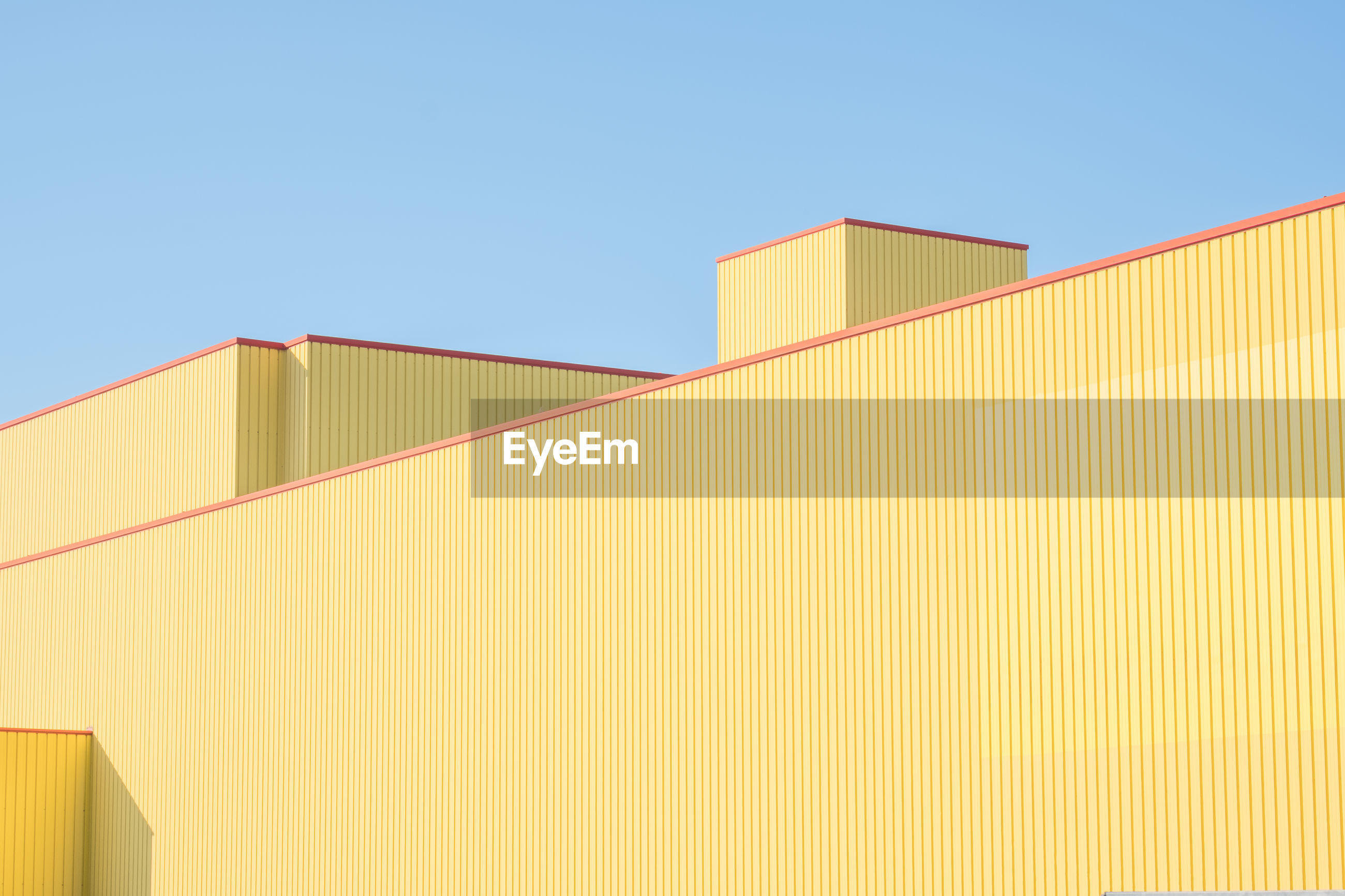 Low angle view of yellow factory building against clear blue sky