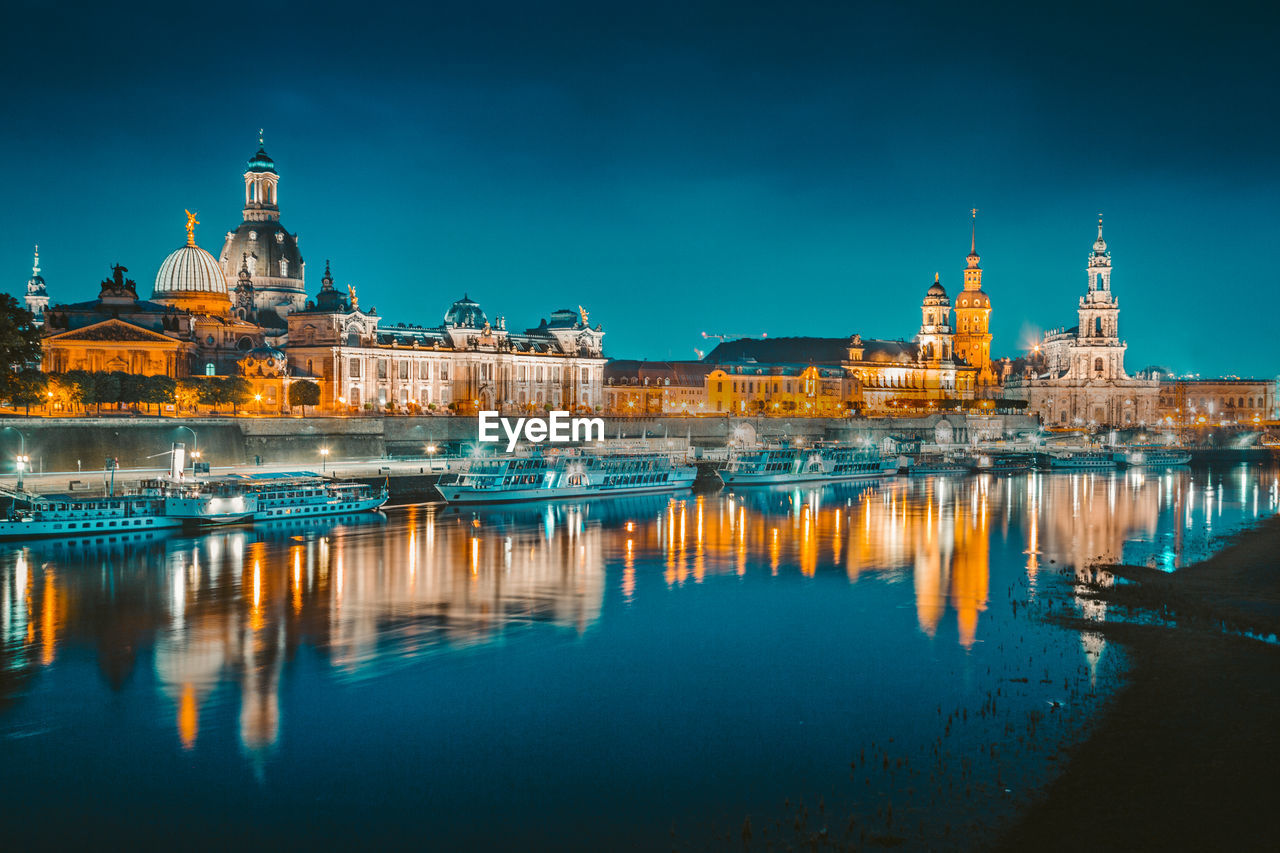 Illuminated buildings by river in city at night