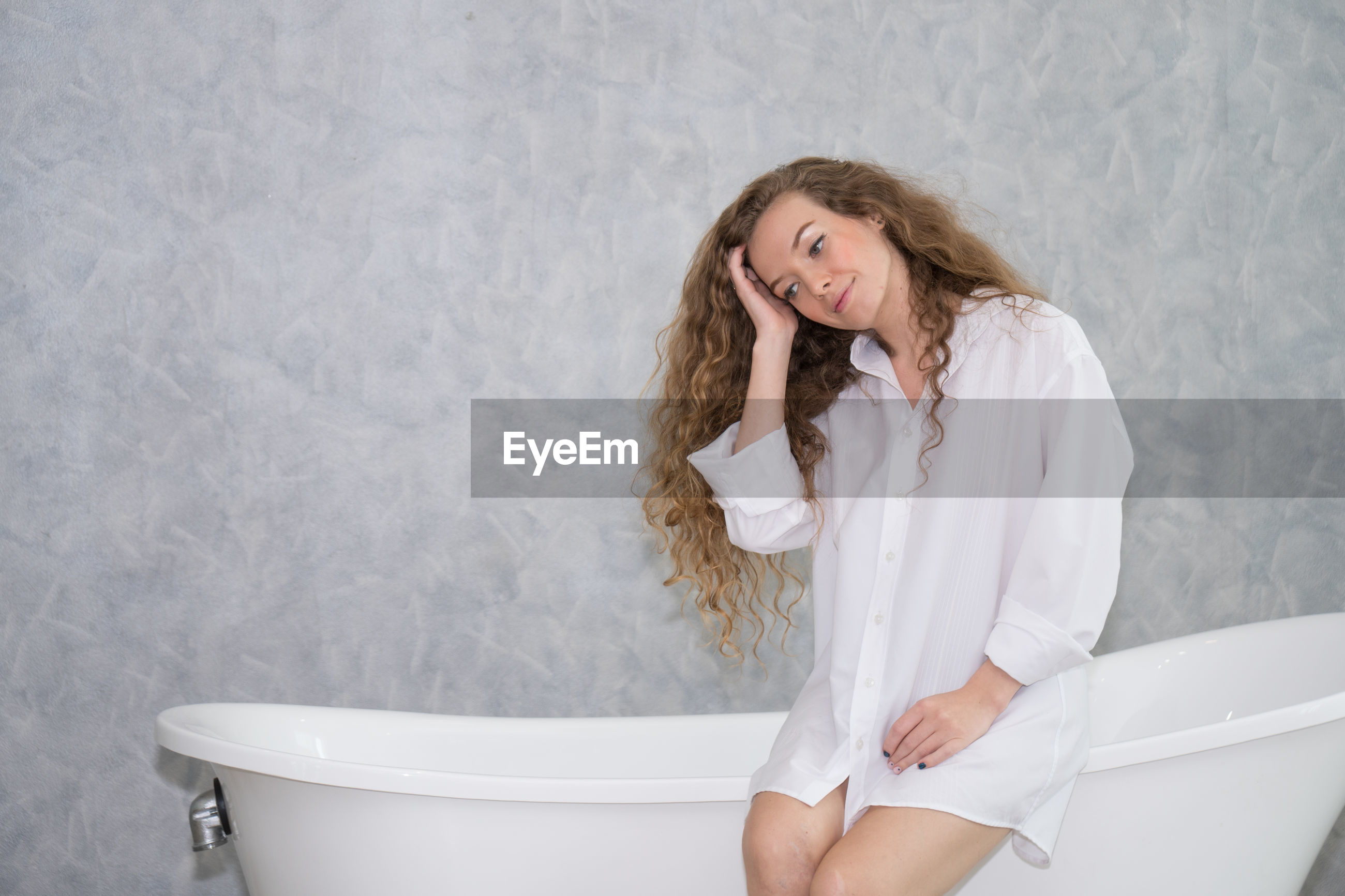 Smiling woman sitting on bathtub against wall