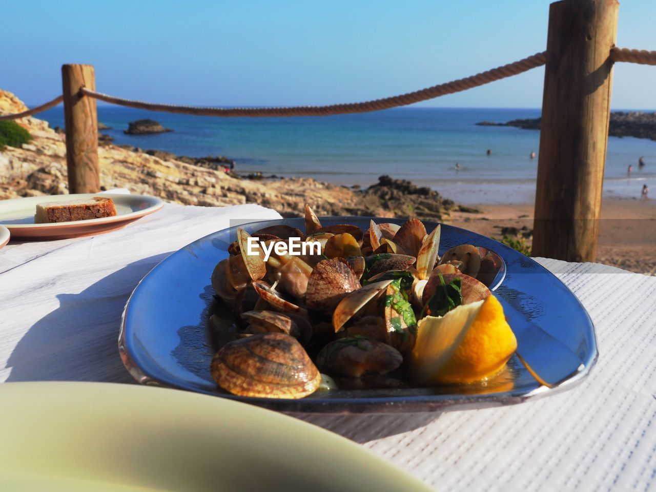 CLOSE-UP OF BREAKFAST ON TABLE BY SEA