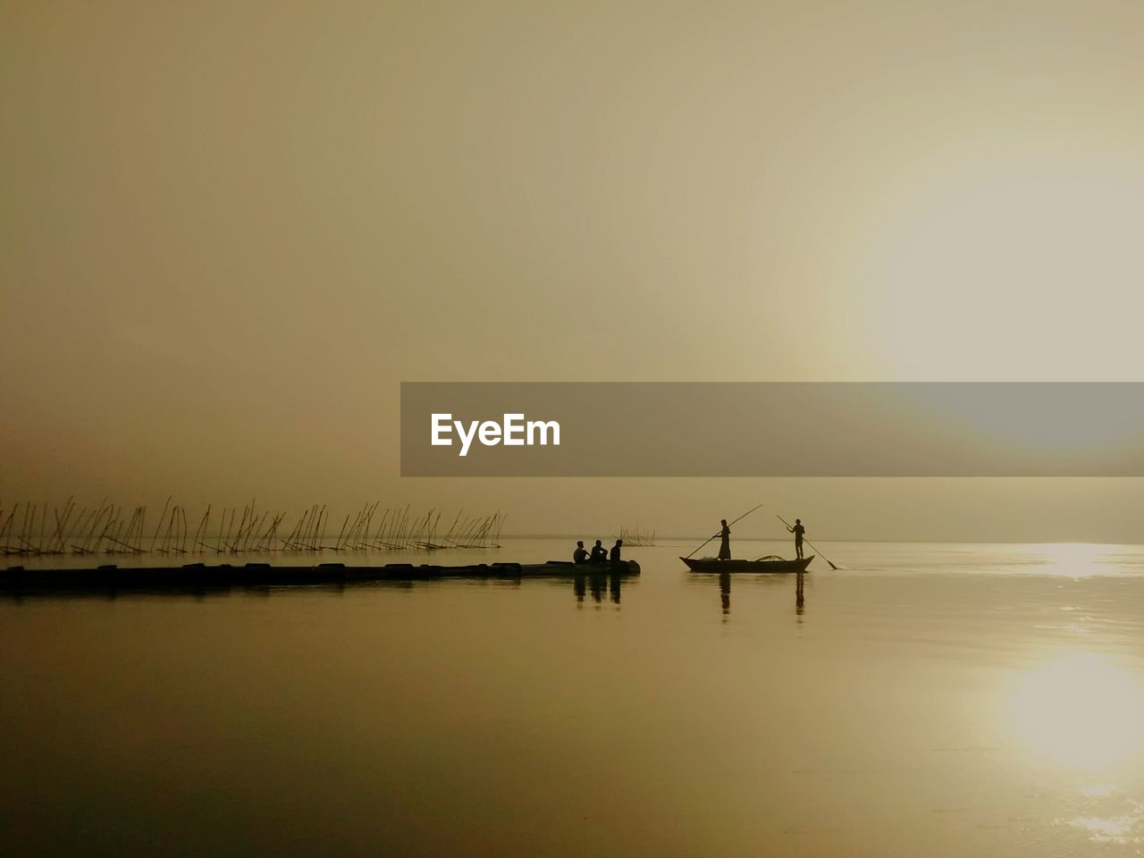 People Rowing Boat In River During Sunrise