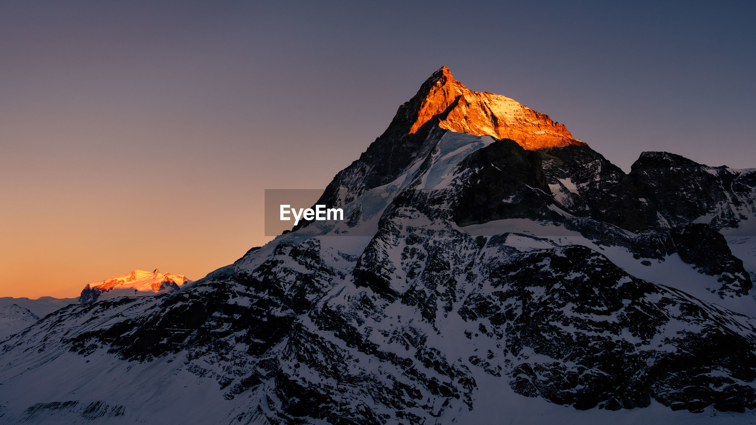 SNOWCAPPED MOUNTAIN AGAINST SKY DURING SUNSET