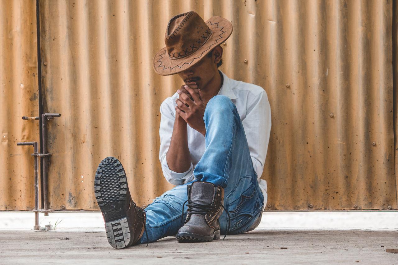 Teenage Boy Wearing Hat Sitting Against Corrugated Iron