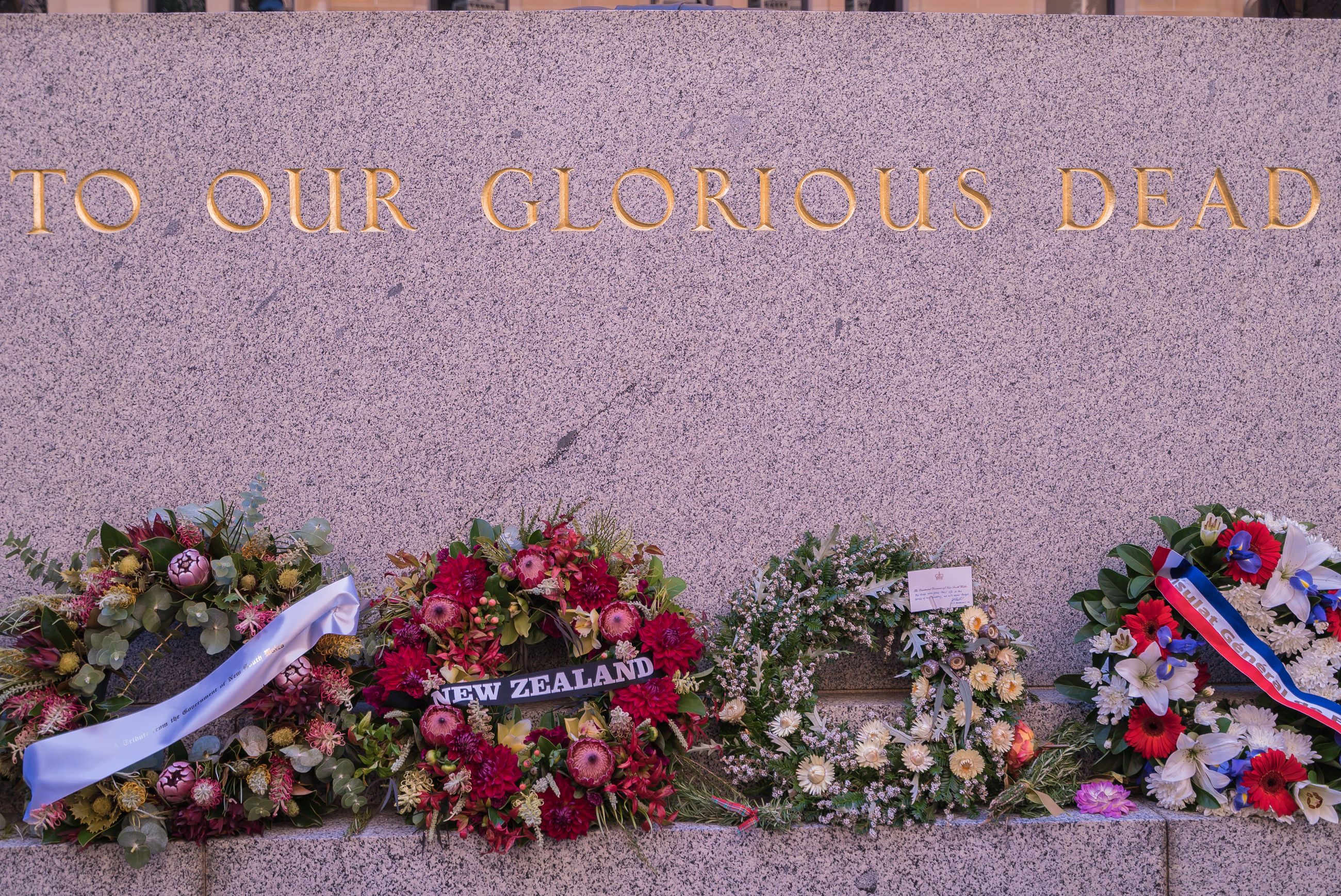 Flower wreaths on tombstone with text
