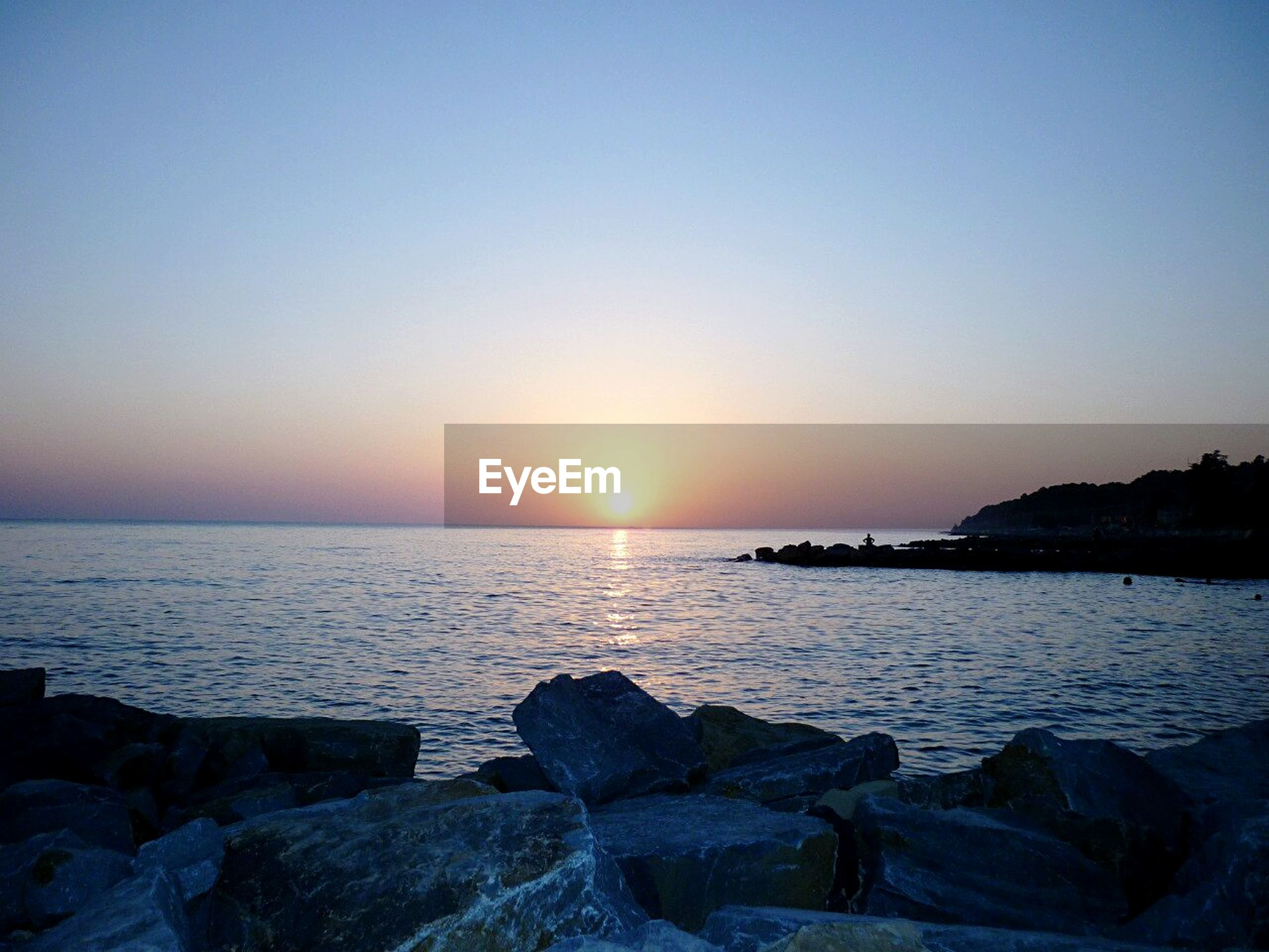 sea, water, sunset, scenics, tranquil scene, horizon over water, beauty in nature, sun, rock - object, tranquility, clear sky, nature, idyllic, shore, rock formation, copy space, beach, rock, silhouette, sky