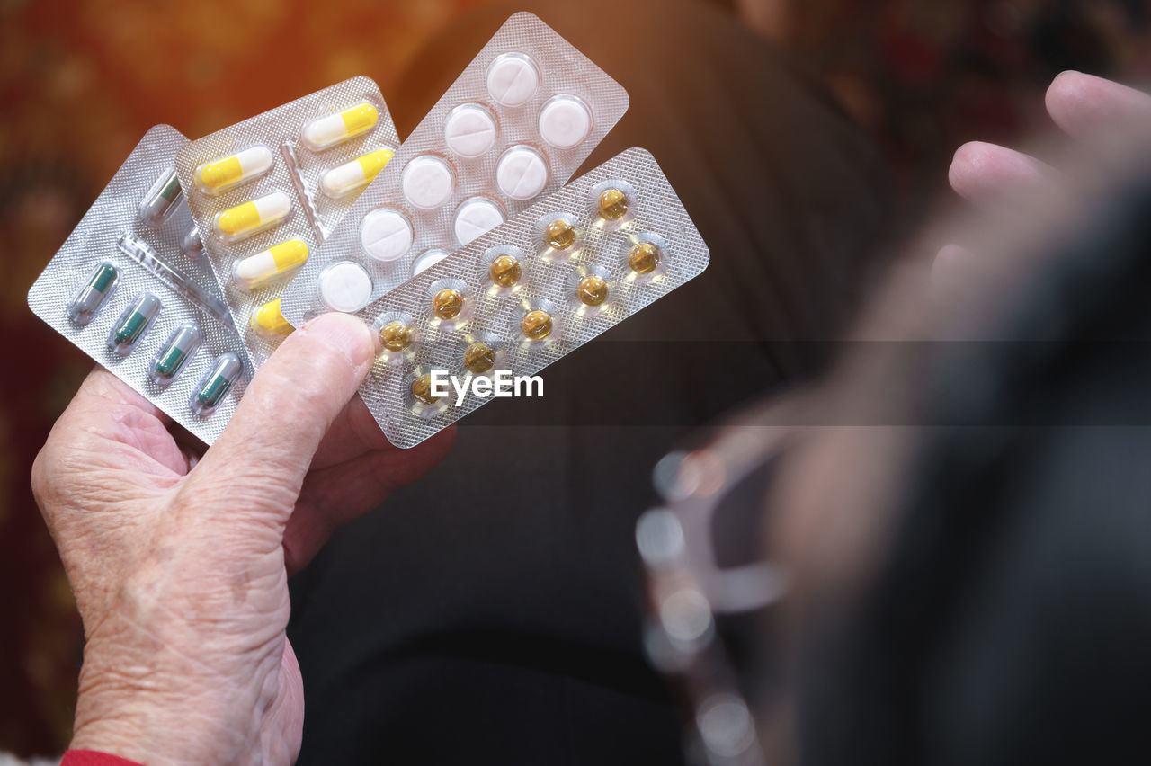 Cropped hand of woman holding medicines