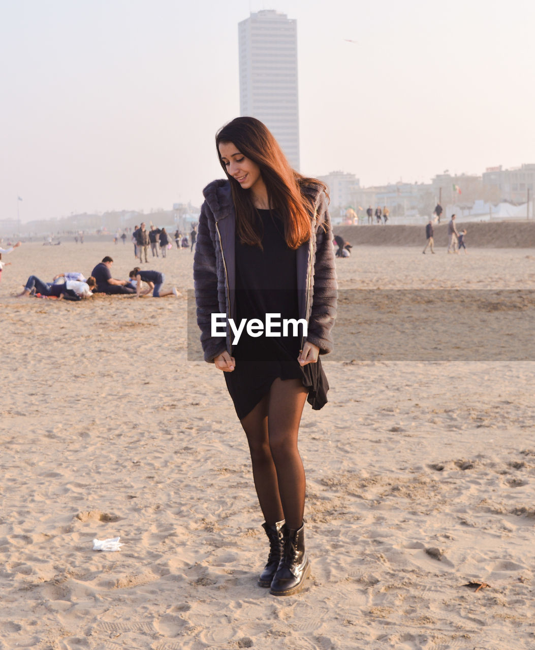 Full length of young woman wearing jacket while standing at sandy beach