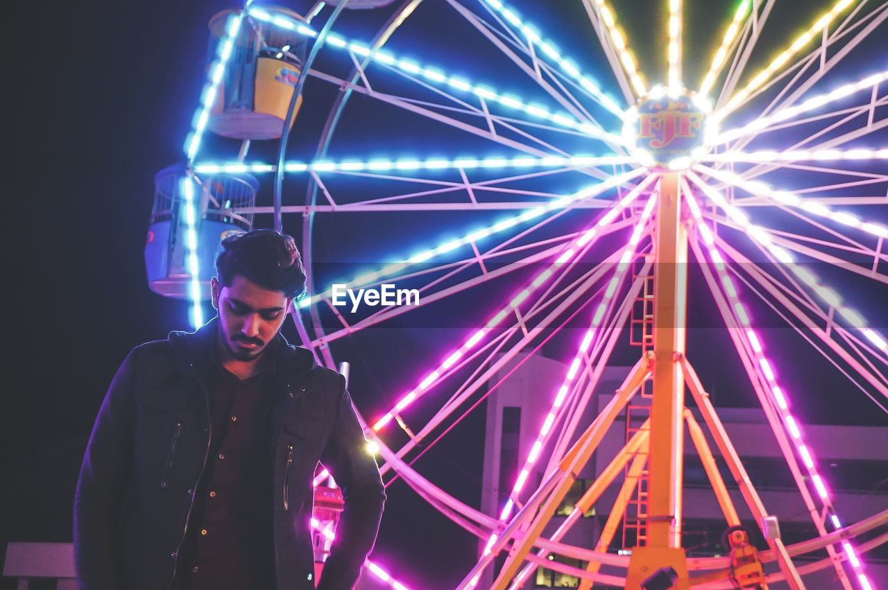 Young Man Standing Against Illuminated Ferris Wheel At Night